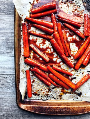 roasted carrots on sheet pan and parchment paper with gochujang glaze