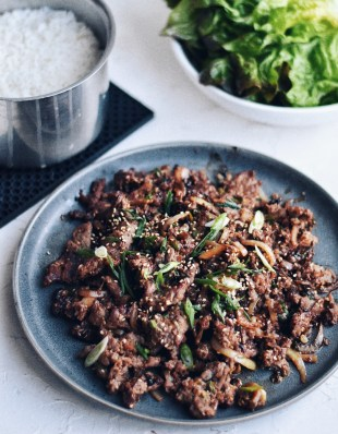 Korean beef bulgogi on a pate with rice and lettuce wraps on the side