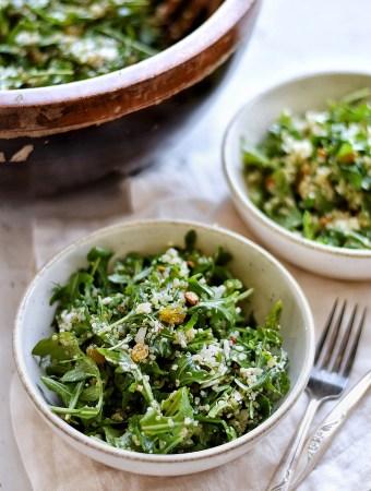arugula quinoa salad in bowl with fork