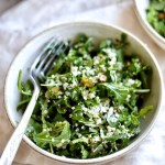 close up of arugula quinoa salad in bowl with fork