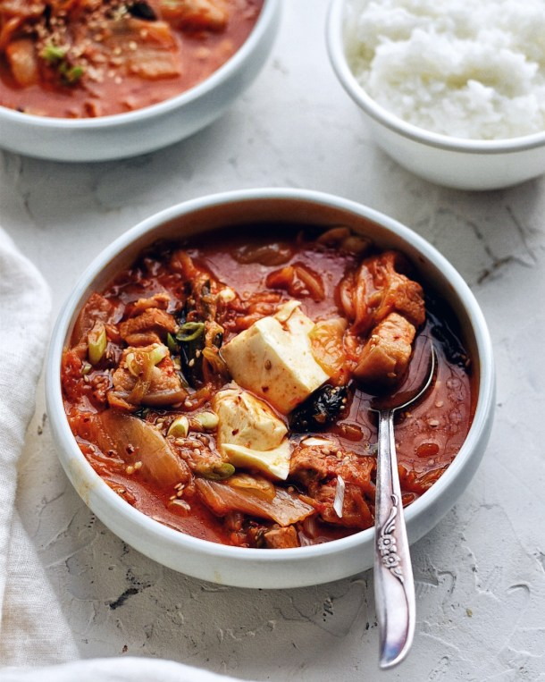 kimchi stew (kimchi jjigae) in a white bowl with spoon