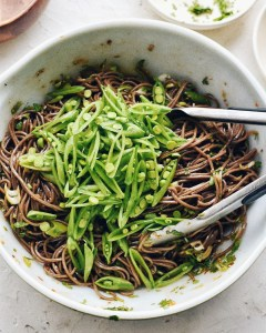 soba noodles with vegetables in bowl and tongs