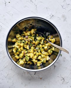 pineapple salsa in stainless steel bowl and spoon