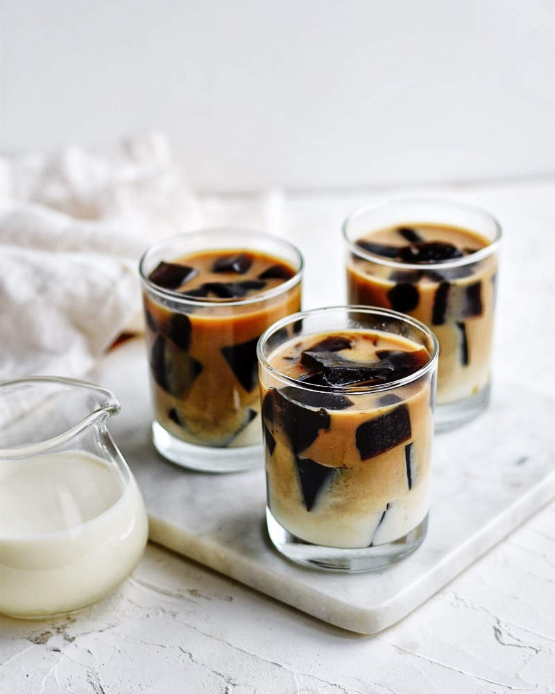 3 glasses of coffee jello staggered on marble board with pitcher of sweet milk on the side
