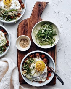 easy kimchi fried rice in bowl with green onion garnish on brown cutting board