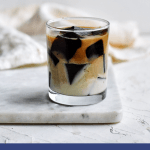 glass cup of coffee jello on white marble board with white napkin in the back