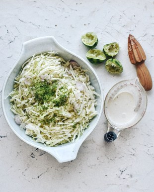 Lime Cilantro coleslaw with dressing and juiced limes and juicer on the side