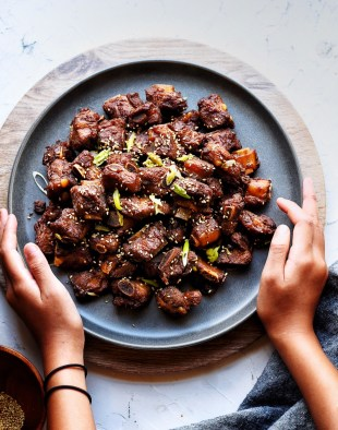 hands holding dark plate with asian pork riblets