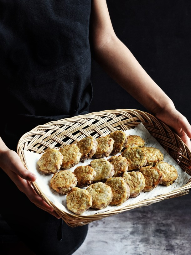 hands holding woven basket with rows of Korean beef patties