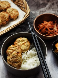bowl of rice with Korean beef patties and chopsticks, bowl of kimchi nearby