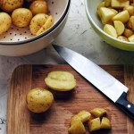 brown cutting board with cut up potatoes and knife and colander in corner