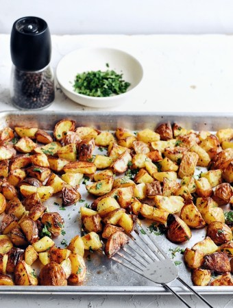 sheet pan with roast potatoes in sheet pan with spatula and pepper mill in background