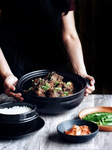 two hands holding a pot of galbi jjim (korean braised short ribs) with dark background