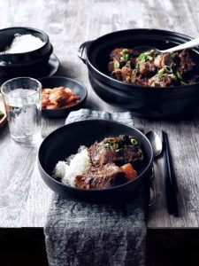 set table with dark bowl filled with rice and galbi jjim (korean braised short ribs) and side dishes