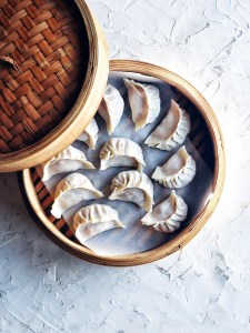 bamboo steamer basket filled with fresh kimchi pork dumplings and lid partially off