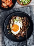 black bowl on a napkin filled with rice, bulgogi, and fried egg