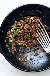 ground beef bulgogi with green onion garnish in cast iron wok with spatula on the side