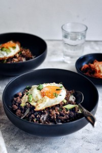 two bulgogi bowls with fried egg on top and side dish of kimchi