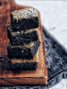 squares of black sesame mochi cake stacked on top of brown cutting board
