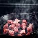 steak cubes smoking in cast iron pan