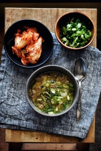 bowl of beef bone soup (gomtang) with kimchi and green onions on the side