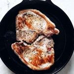 two browned pork chops in cast iron pan