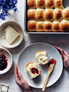 soft dinner rolls with butter and jam on a plate