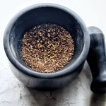 mortar and pestle filled with sichuan peppercorns