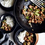 spicy sichuan chicken stir fry in wok and small bowls on the side
