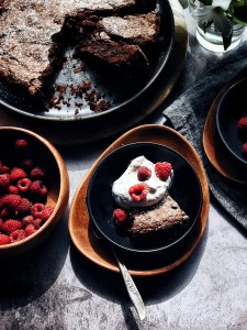 table set with dessert of chocolate almond cake, whipped cream, raspberries