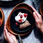two hands on plate of chocolate almond cake with whipped cream and raspberries