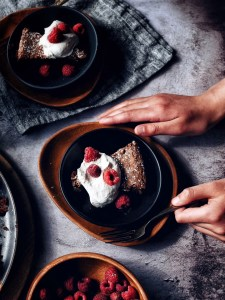 chocolate cake with whipped cream and raspberries on plate and hands on the side