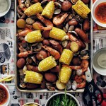 seafood boil elements on tray: corn, sausage, clams, shrimp