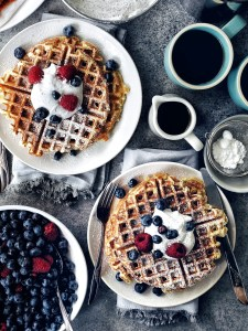 two plates with buttermilk waffles and berries
