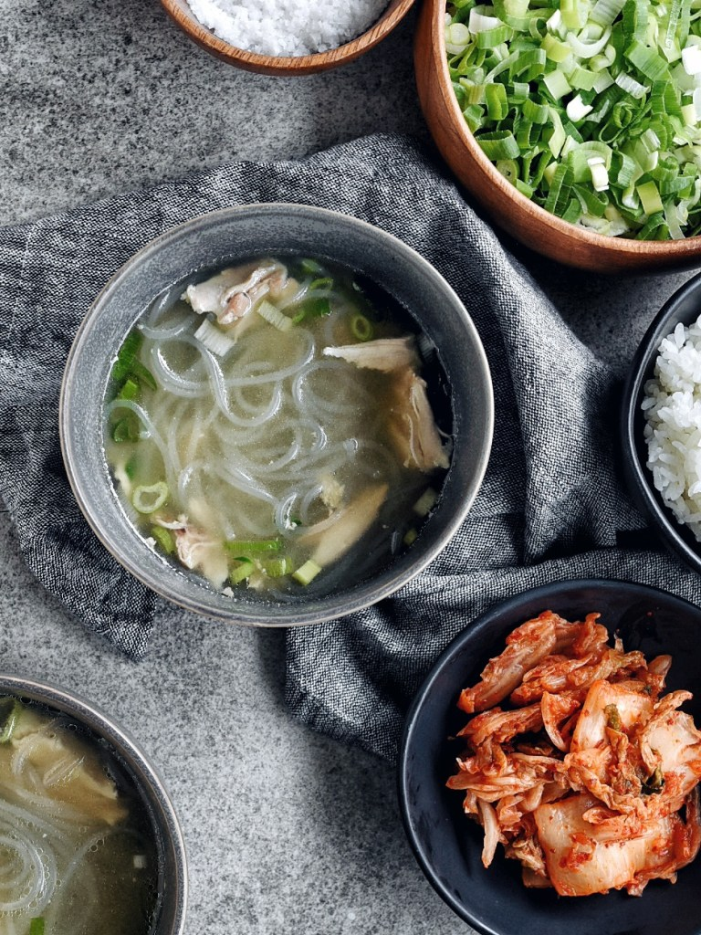 bowl of korean chicken soup (dak gomtang) in grey bowl with kimchi on the side