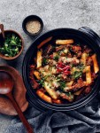 spicy galbi jjim in a black pot, with cheese