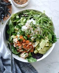 salmon poke bowl with salad base in white bowl