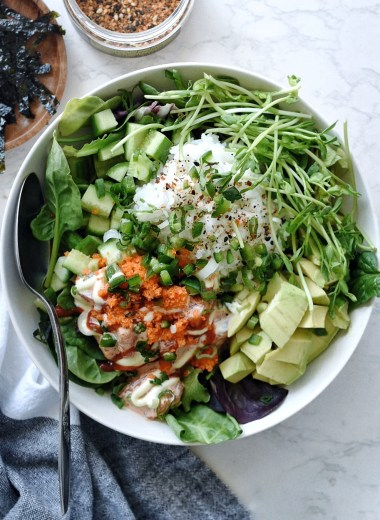 salmon poke bowl with salad base in white bowl
