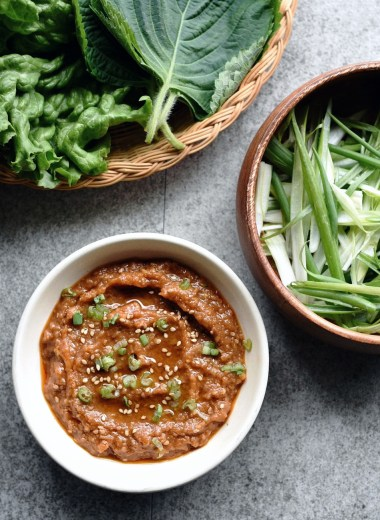 small bowl of ssamjang with green onions and lettuce wraps