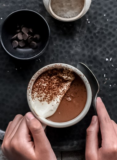 hands holding teacup filled with dark chocolate mousse and vegan cashew cream