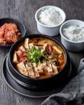 bowl of korean soybean paste stew (doenjang jjigae) with two bowls of rice