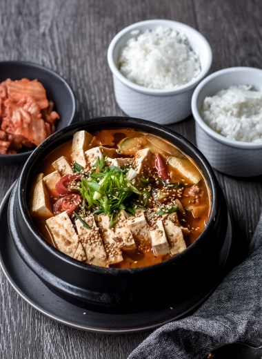 bowl of korean soybean paste stew (doenjang jjigae) with two bowls of rice