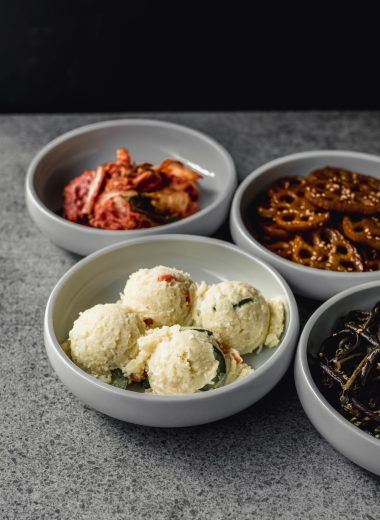 korean potato salad in round dish, served alongside other side dishes