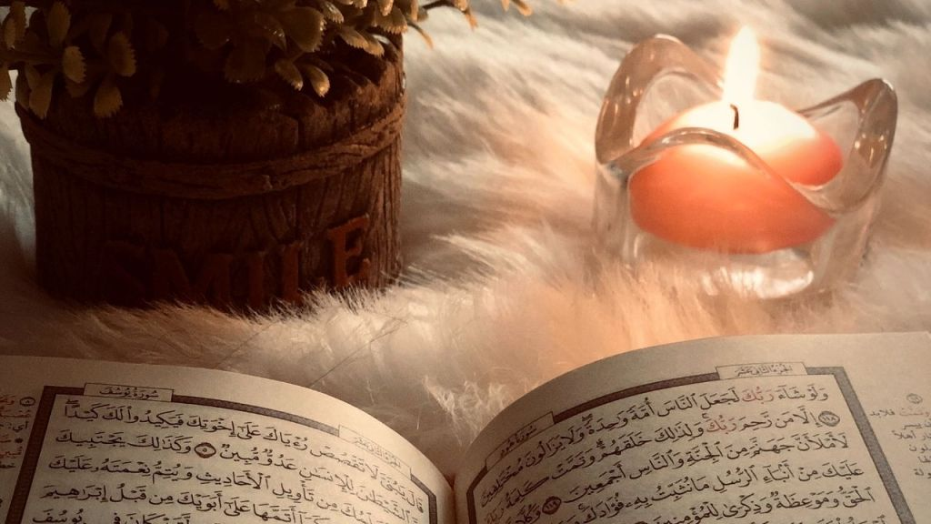 Quran on a soft carpet with a pink candle and plant pot
