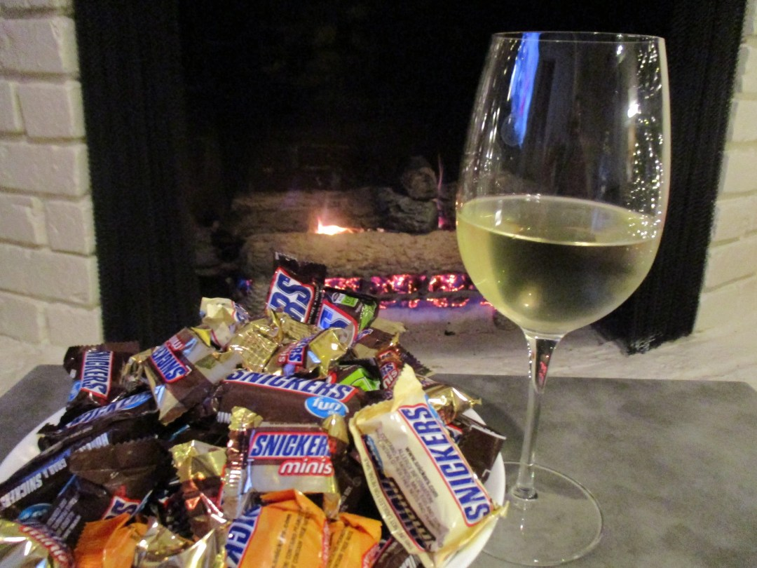 Bowl of Snickers with glass of wine in front of fire