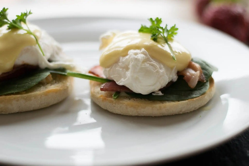Eggs benedict on white plate