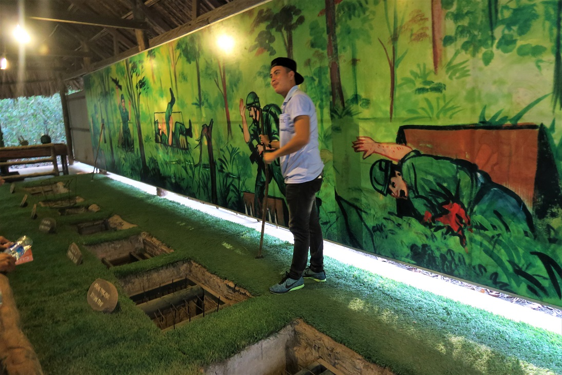 Tour Guide explaning trap doors in Cu Chi tunnels Budget Breakdown Solo Travel in South Vietnam