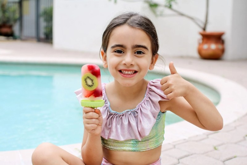 girl holding a fresh fruit popsicle and giving the thumbs up