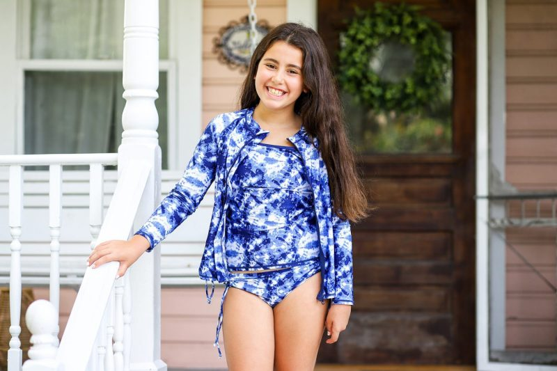 Beautiful girl wearing a rash guard and swimwear from SwimZip on a porch
