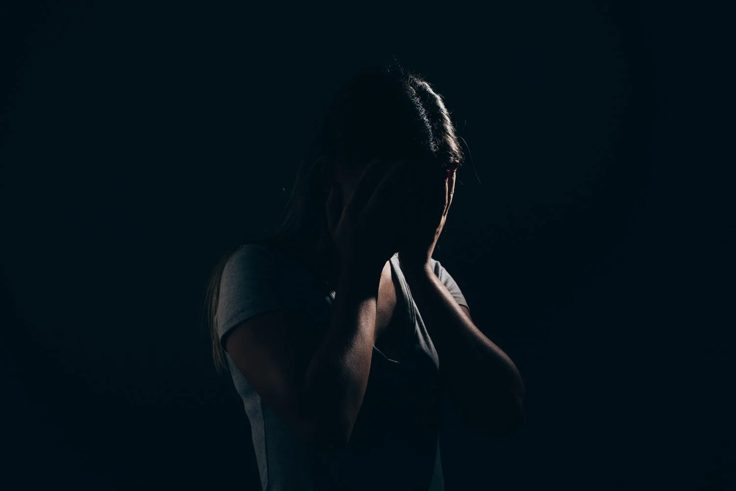 Sad woman in dark room. Depression and anxiety disorder concept